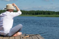 De mens zit op een houten pijler voor visserij het gebruikende spinnen op de rivier stock afbeelding