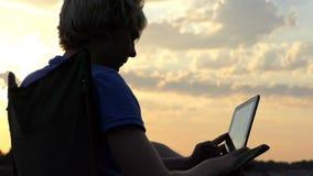 De mens zit op een Vouwende Stoel en bekijkt Zijn Tabletpc Zonsondergang in slo-Mo stock video