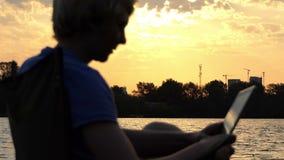 De mens zit op een Vouwende Stoel en bekijkt Zijn Tabletpc Zonsondergang uit nadruk stock footage