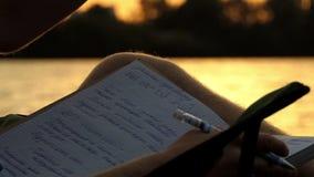 De mens zit op een Vouwende Stoel op Riverbank, leest Zijn Nota's bij Zonsondergang stock videobeelden