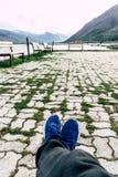 De mens zit op houten bank bij bergmeer gras in de bestrating, bergen bij horizon en vallei Benen in sportschoenen royalty-vrije stock foto