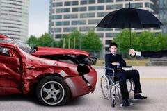 De mens zit op rolstoel met beschadigde auto stock foto