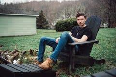 De mens zit in openlucht op een houten stoel op de binnenplaats van zijn huis bij plattelandsgebied royalty-vrije stock afbeeldingen