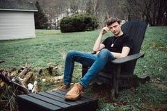 De mens zit in openlucht op een houten stoel op de binnenplaats van zijn huis bij plattelandsgebied royalty-vrije stock foto's
