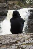 De mens zit vreedzaam bij rustige waterval Royalty-vrije Stock Foto's