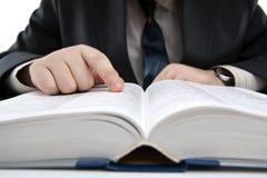 De mens zoekt informatie in het woordenboek Stock Foto