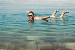 De mens in zonnebril stelt als vliegtuig op oppervlakte Dode Overzees Vrije tijd, vakantie, Wellness-toerisme, recreatieconcept Stock Afbeeldingen