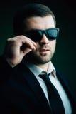 De mens in zonnebril verminderde een weinig in de donkere ruimte Stock Foto