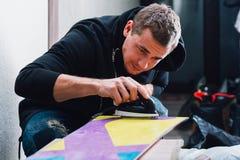 De mens is zorgvuldig in de was zettend snowboard royalty-vrije stock foto