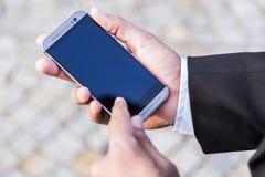 De mens in zwart kostuum houdt mobiele telefoon in zijn hand royalty-vrije stock afbeelding