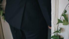 De mens in zwart kostuum opent witte oude uitstekende die deur met messingshandvat met groene klimop wordt verfraaid De mens duwt stock video