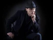 De mens in zwarte doek denkt met ernstige blik Stock Afbeeldingen