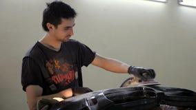 De mens in zwarte handschoenen werkt met luchtschuurmachine bij de dienst van het autolichaam, bumper stock video