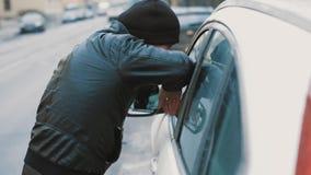 De mens in zwarte jasje en beanie hoed leunt op autoraam bij stad stock video