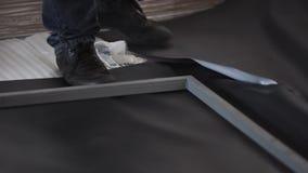 De mens in zwarte schoenen en donkere jeans bevindt zich op zwart blad en grijs metaalkader stock footage