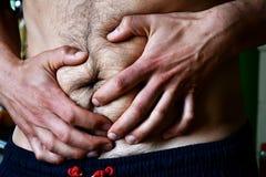 De mens in zweetkostuum heeft maagproblemen royalty-vrije stock afbeelding