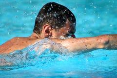 De mens zwemt in blauw water Stock Foto