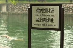 De mens zwemt dichtbij teken 'verboden zwemmen' Royalty-vrije Stock Foto's
