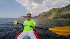 De mens zwemt in het overzees in een kajak stock video