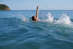 De mens zwemt terug Stock Foto