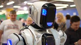 De menselijke androïde mensen van de gangmenigte tonen technologiemogelijkheden in tentoonstellingszaal stock video