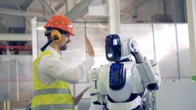 De menselijke fabrieksarbeider en androïde geven elkaar hallo-vijf bij een fabrieksfaciliteit stock video