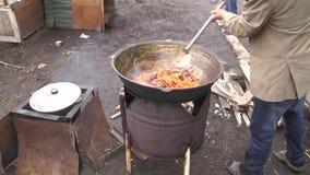 De menselijke hand beweegt kokende olie met vlees en kruiden met een houten peddel, voorbereiding van pilau, vooraanzicht stock video