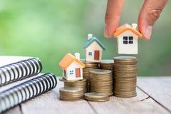 De menselijke hand die huismodel op muntstukken zetten stapelt, van plan zijnd besparingengeld van muntstukken om een huisconcept stock afbeelding