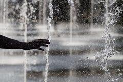 De menselijke hand en de fontein van ` s Stock Foto