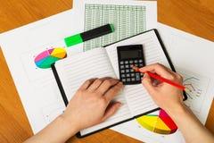 De menselijke hand met potlood en calculator vindt notitieboekje op Desktop Stock Afbeeldingen