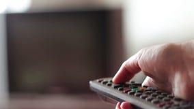 De menselijke hand verandert de kanalen op de TV-afstandsbediening stock video