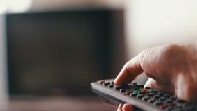 De menselijke hand verandert de kanalen op de TV-afstandsbediening stock videobeelden