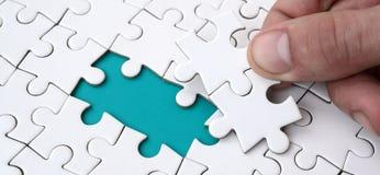 De menselijke hand vult de laatste ontbrekende elementen van de oppervlakte vanaf de puzzel Het concept de voltooiing van stock afbeelding