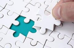 De menselijke hand vult de laatste ontbrekende elementen van de oppervlakte vanaf de puzzel Het concept de voltooiing van royalty-vrije stock foto's