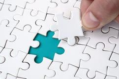 De menselijke hand vult de laatste ontbrekende elementen van de oppervlakte vanaf de puzzel Het concept de voltooiing van stock fotografie