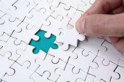 De menselijke hand vult de laatste ontbrekende elementen van de oppervlakte vanaf de puzzel Het concept de voltooiing van royalty-vrije stock afbeelding