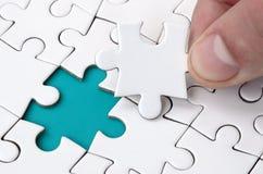 De menselijke hand vult de laatste ontbrekende elementen van de oppervlakte vanaf de puzzel Het concept de voltooiing van royalty-vrije stock foto
