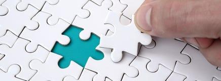 De menselijke hand vult de laatste ontbrekende elementen van de oppervlakte vanaf de puzzel Het concept de voltooiing van stock foto's