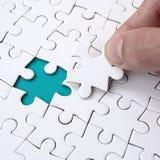 De menselijke hand vult de laatste ontbrekende elementen van de oppervlakte vanaf de puzzel Het concept de voltooiing van stock afbeeldingen