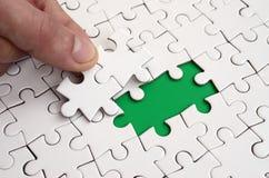 De menselijke hand vult de laatste ontbrekende elementen van de oppervlakte vanaf de puzzel Het concept de voltooiing van initiat stock foto