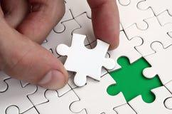 De menselijke hand vult de laatste ontbrekende elementen van de oppervlakte vanaf de puzzel Het concept de voltooiing van initiat royalty-vrije stock fotografie