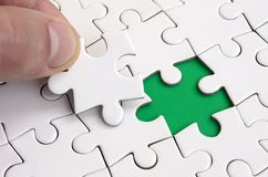 De menselijke hand vult de laatste ontbrekende elementen van de oppervlakte vanaf de puzzel Het concept de voltooiing van initiat Royalty-vrije Stock Afbeelding