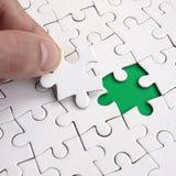 De menselijke hand vult de laatste ontbrekende elementen van de oppervlakte vanaf de puzzel Het concept de voltooiing van initiat Royalty-vrije Stock Afbeeldingen