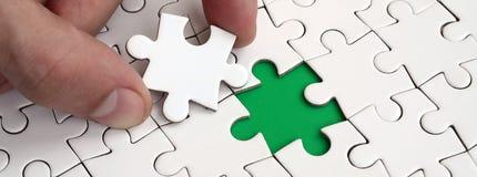 De menselijke hand vult de laatste ontbrekende elementen van de oppervlakte vanaf de puzzel Het concept de voltooiing van initiat Stock Afbeelding