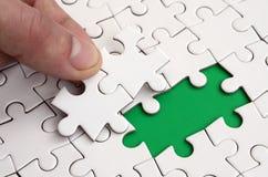 De menselijke hand vult de laatste ontbrekende elementen van de oppervlakte vanaf de puzzel Het concept de voltooiing van initiat Royalty-vrije Stock Foto