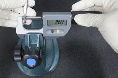 De menselijke meting van de gebruiks digitale micrometer een rode balsonde Royalty-vrije Stock Afbeeldingen