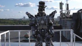 De menselijke robot in al groei wordt gedreven door lidmaten op achtergrond van blauwe hemel met wolken lengte Android met gezich stock footage