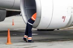 De menselijke technicusingenieur controleert het het vliegtuigblad van de turbinemotor ` s na de reis en psodki in het parkeren b Stock Foto