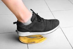 De menselijke voet van ` s glijdt op de schil van een heerlijke, verse, tropische heldere gele banaan op de vloer Veiligheid en a royalty-vrije stock fotografie
