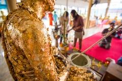 De mensen aanbidden het Standbeelddekking van Boedha met bladgoud in tempel royalty-vrije stock afbeelding